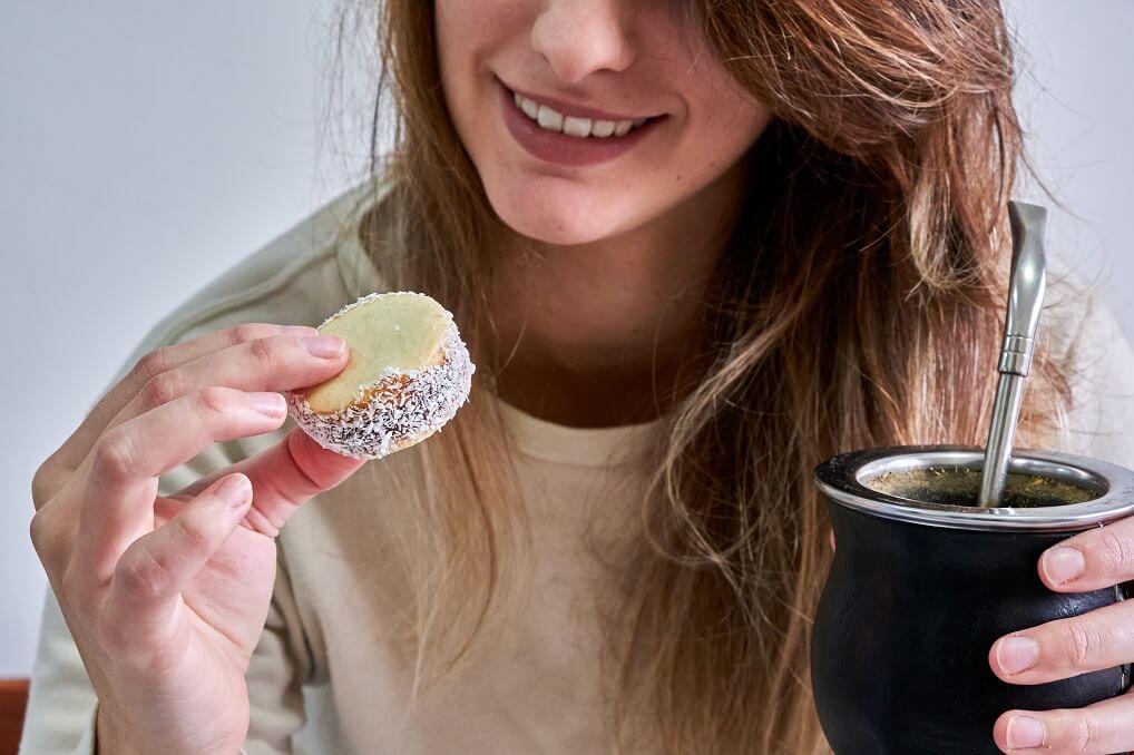 Frau isst Maismehl-Alfajor und trinkt Mate Tee aus einer Kalabasse.