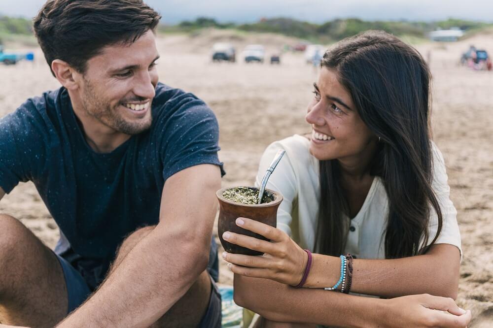 Glückliches junges Paar teilen Yerba Mate Kräutertee am Strand.